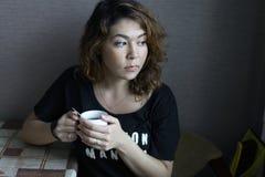 Flickan dricker kaffe i det orientaliska köket Arkivbilder