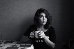 Flickan dricker kaffe i det orientaliska köket Royaltyfri Bild
