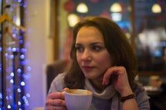 Flickan dricker kaffe i ett kafé Fotografering för Bildbyråer