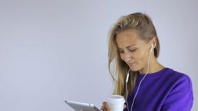 Flickan dricker kaffe och använder en minnestavla lager videofilmer