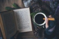 Flickan dricker kaffe och läser boken arkivbild
