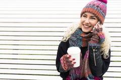 Flickan dricker kaffe och samtal på telefonen utomhus Arkivfoton