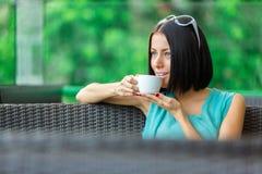 Flickan dricker kaffe på stången royaltyfri foto
