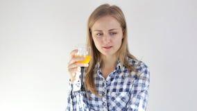 Flickan dricker ny orange fruktsaft och ser in i kameran arkivfilmer