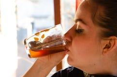 Flickan dricker te fr?n en genomskinlig kopp i eftermiddagen p? gatan royaltyfri fotografi