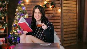 Flickan dricker te i studion lager videofilmer