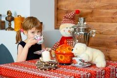 Flickan dricker te och att le arkivfoto