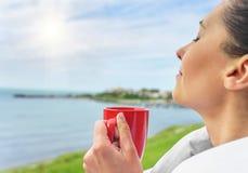 Flickan dricker te på ett bakgrundshavslandskap arkivbild