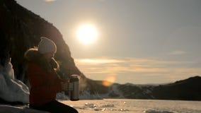 Flickan dricker te på solnedgången arkivfilmer
