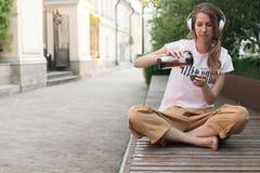 Flickan dricker te som lyssnar till musik med soligt väder royaltyfri bild