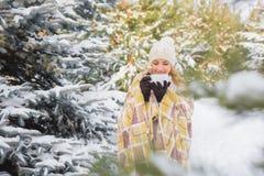 Flickan dricker utomhus i vinterskog royaltyfria foton