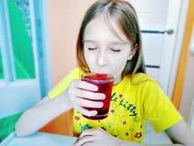 Flickan dricker vatten med stycken av fruktis royaltyfri fotografi