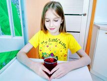 Flickan dricker vatten med stycken av fruktis royaltyfria bilder