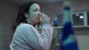 Flickan dricker vin från ett exponeringsglas hålla ögonen på för tv Ett parti arkivfilmer