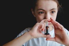 Flickan dryper in i hennes näsa med en sprej av förkylning arkivbilder
