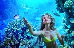 Flickan dyker under vatten bland korall Arkivbilder