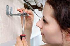 Flickan fäster vertikala rullgardiner för skruvmejselkonsolen till väggen royaltyfri fotografi