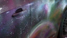 Flickan får en målarfärg från en behållare på en vit bilkropp stock video