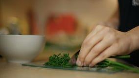 Flickan för den unga kvinnan skivar dill på ett glass bräde i köket lager videofilmer