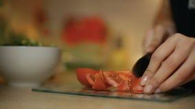 Flickan för den unga kvinnan skivar en tomat på ett glass bräde i köket stock video