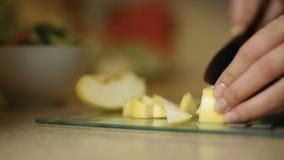Flickan för den unga kvinnan skivar ett äpple på ett glass bräde i köket stock video