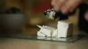 Flickan för den unga kvinnan skivar fetaost på ett glass bräde i köket stock video