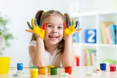 Flickan för det härliga barnet med händer i färg målar arkivfoto