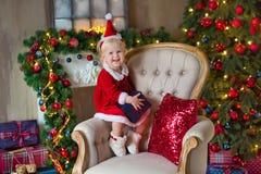 Flickan för det lilla barnet för glad jul och för lyckliga ferier dekorerar den gulliga julgranen inomhus royaltyfria foton