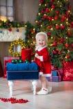 Flickan för det lilla barnet för glad jul och för lyckliga ferier dekorerar den gulliga julgranen inomhus royaltyfria bilder