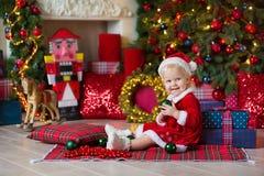 Flickan för det lilla barnet för glad jul och för lyckliga ferier dekorerar den gulliga julgranen inomhus royaltyfri bild