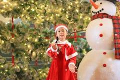 Flickan för det lilla barnet i santa dräktklänning har gyckel och lek med snö på vintertid mot julbakgrund glad jul royaltyfri foto