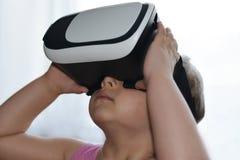 Flickan för det lilla barnet spelar en lek med virtuell verklighetexponeringsglas på vit bakgrund, ökad verklighet, hjälmen, data royaltyfri fotografi