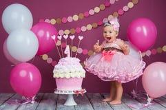 Flickan för födelsedagen för liten flicka` s suddades in i en kaka Den första kakan Bruket av den första kakan Dundersuccékaka royaltyfria bilder