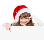 Flickan för lycklig jul med den santa hatten pekar ner Isolerat på whi fotografering för bildbyråer