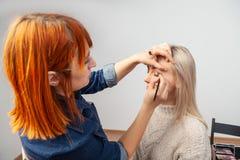 Flickan för makeupkonstnären med rött hår och en borste i hennes hand lägger på smink på modellens ögon - skuggor av guld- färg i royaltyfri bild