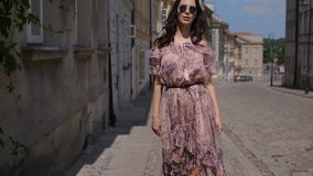 Flickan för modehipsterstil går till och med sommarstadsgatorna arkivfilmer