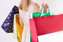 Flickan för modemodellen med att shoppa färgrika påsar i händer och kräm snör åt klänningen arkivbilder