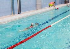 Flickan för skolaåldern simmar i pöl med brädet Unga ungar som simmar utbildning i rysk sportskola Arkivbild