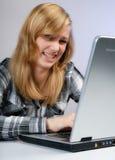 Flickan förargas av datoren Arkivbild