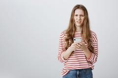 Flickan förargas med skräppost på hennes brevlåda Stående av den hållande smartphonen för besvärad och förvirrad caucasian kvinna arkivfoto