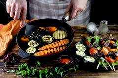 Flickan förbereder grillade grönsaker i en gjutjärnkastrull royaltyfria bilder
