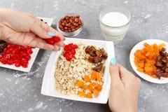 Flickan förbereder hennes mysli för frukost som den torkade flickan sätter sig - bära frukt i havremjölhavregröt Användbar och su royaltyfria foton