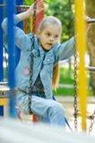 Flickan försöker att klättra från en hängande stege till andra på lekplatsen arkivfoto