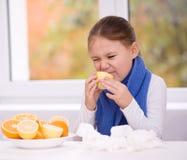 Flickan försöker att smaka en skiva av apelsinen Royaltyfria Foton