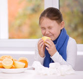 Flickan försöker att smaka en skiva av apelsinen Arkivbilder