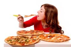 Flickan försöker olika sorter av pizza Arkivbilder