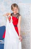 Flickan försöker på en bröllopsklänning Royaltyfri Bild