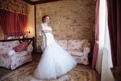 Flickan försöker på en bröllopsklänning och visar upp i hennes rum Bruden ler se ut fönstret Royaltyfria Bilder