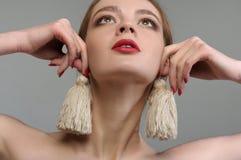 Flickan försöker på själv-gjorda örhängen från trådar Royaltyfri Bild