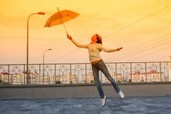 Flickan flyger med ett paraply Royaltyfri Bild